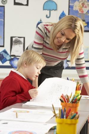 maestra ense�ando: Alumnos de la escuela primaria masculina y profesor funcionan a atenci�n al cliente en el aula Foto de archivo