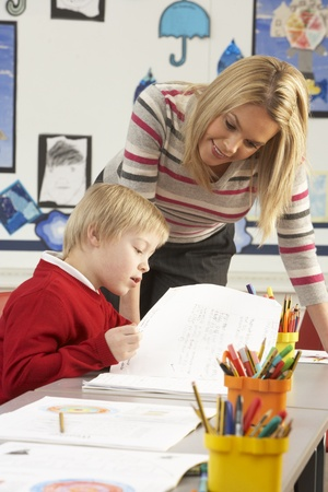 tutoring: Male Primary School Pupil And Teacher Working At Desk In Classroom