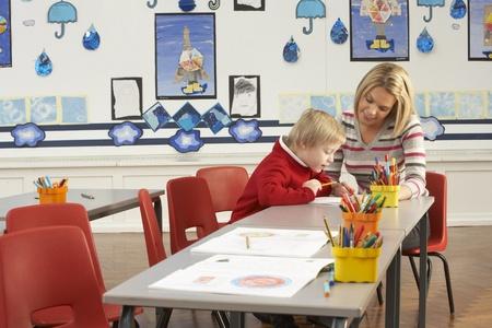schooler: Pupilla di scuola elementare maschile e insegnante di lavoro alla reception In Aula