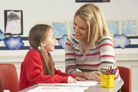 tutor: Femenina de la escuela primaria de alumnos y maestros que funcionan a atenci�n al cliente en el aula Foto de archivo