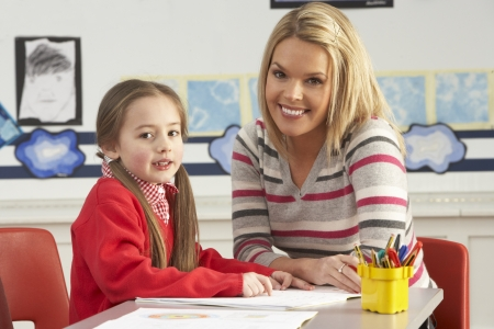 primary colours: Female Primary School Pupil And Teacher Working At Desk In Classroom Stock Photo