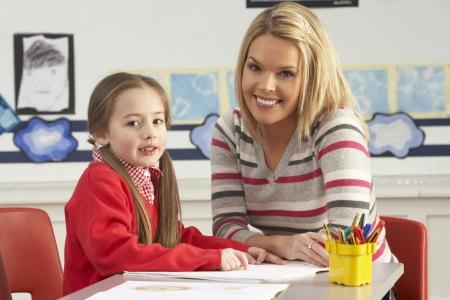 schooler: Femmina allievo della scuola elementare e insegnante di lavorare alla scrivania In Aula