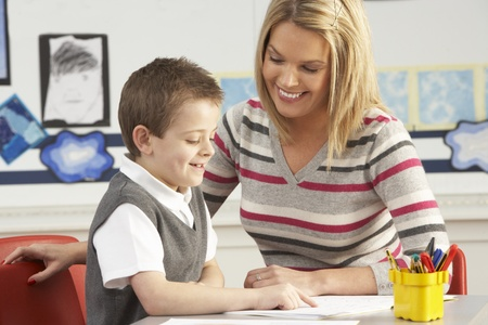 grade schooler: Male Primary School Pupil And Teacher Working At Desk In Classroom