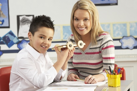 grade schooler: Male Primary School Pupil And Teacher Working At Desk In Classroom