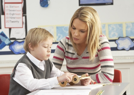 Male Primary School Pupil And Teacher Working At Desk In Classroom photo