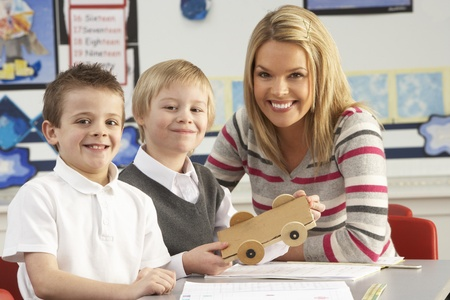 Two Male Primary School Pupils And Teacher Working At Desk In Classroom photo