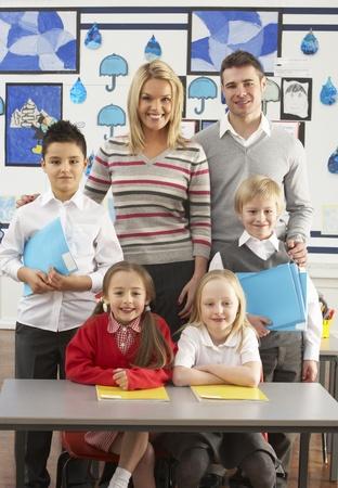 grade schooler: Portrait Of Group Of Primary Schoolchildren And Teachers Sitting At Desk In Classroom Stock Photo