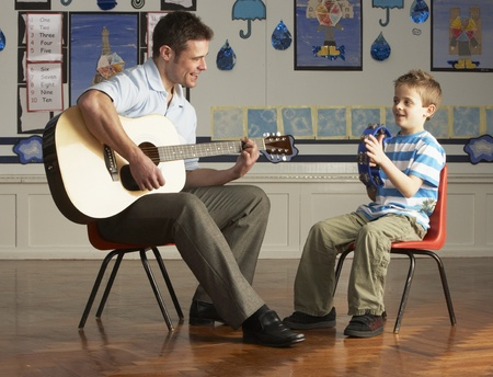teacher in class: Male Teacher Playing Guitar With Pupil In Classroom
