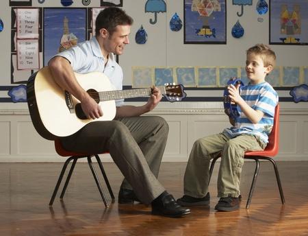 docenten: Mannelijke leraar spelen gitaar met leerling In de klas