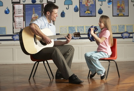 teaching music: Male Teacher Playing Guitar With Pupil In Classroom