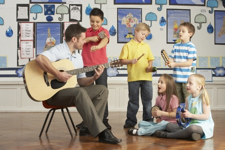grade schooler: Male Teacher Playing Guitar With Pupils Having Music Lesson In Classroom