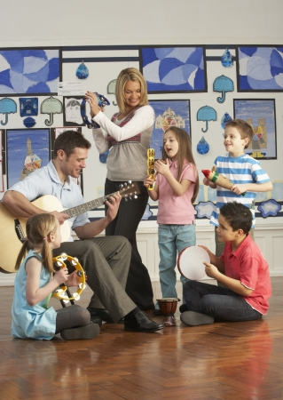 primary colours: Teachers Playing Guitar With Pupils Having Music Lesson In Classroom
