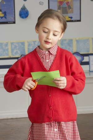 grade schooler: Female Primary School Pupil Cutting Out Paper Shapes In Craft Lesson