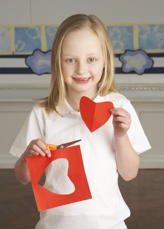 paper craft: Corte femenino de alumno de la escuela primaria las formas de papel en embarcaciones de lecci�n Foto de archivo
