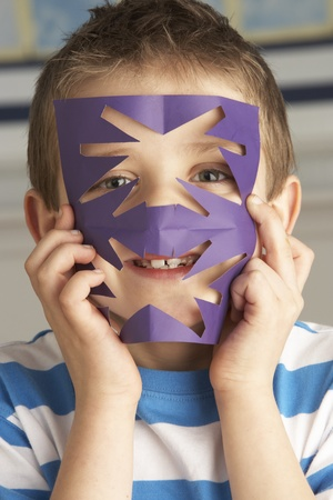 Male Primary School Pupil Cutting Out Paper Shapes In Craft Lesson photo