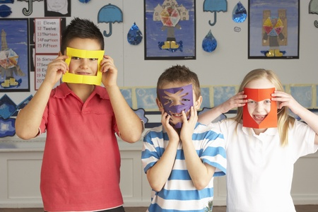 non uniform: Group Of Primary School Children Cutting Out Paper Shapes In Craft Lesson