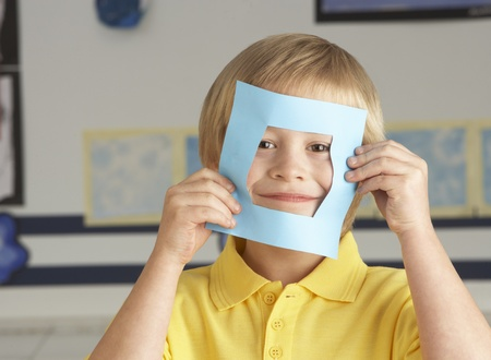 non uniform: Male Primary School Cutting Out Paper Shapes In Craft Lesson Stock Photo