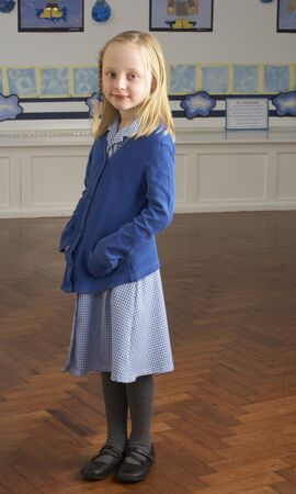 Portrait Of Female Primary School Pupil Standing In Classroom photo