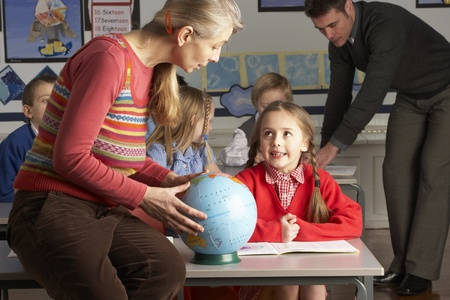 schooler: Teachers Giving Geography Lesson To Primary School Children In Classroom