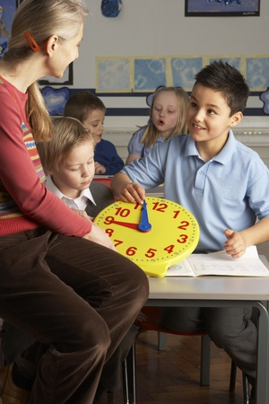 grade schooler: Female Teacher In Primary School Teaching Children To Tell Time In Classroom