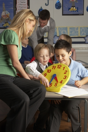 grade schooler: Female Teacher In Primary School Teaching Children To Tell Time In Classroom