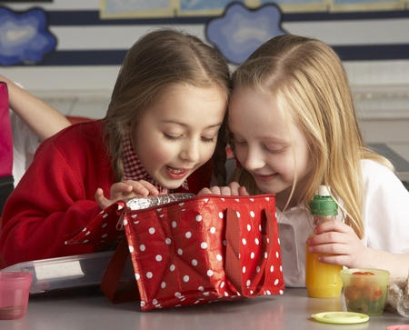 oběd: Primary School Pupils Enjoying Packed Lunch In Classroom