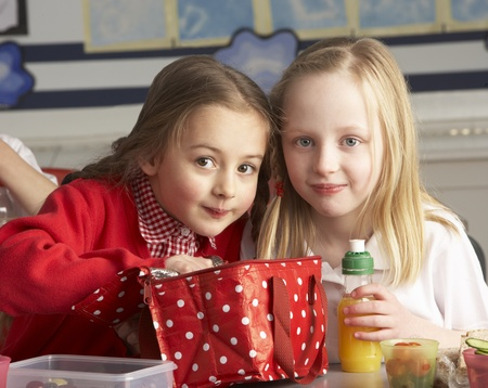 7 year old girl: Primary School Pupils Enjoying Packed Lunch In Classroom