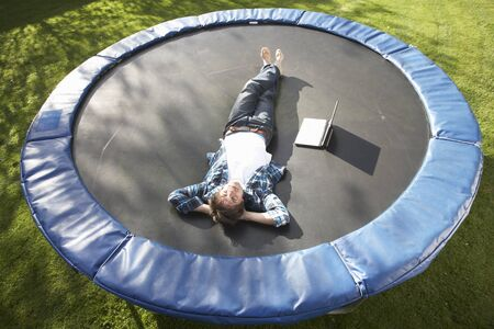 Young Man Relaxing On Trampoline With Laptop photo