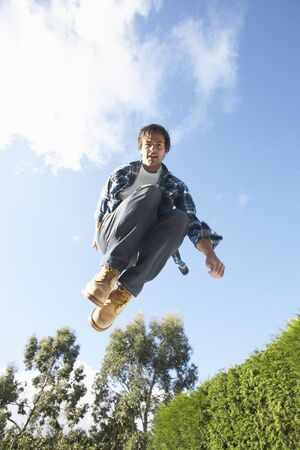 Young Man Jumping On Trampoline Caught In Mid Air photo