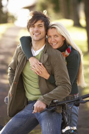 Portrait Of Young Couple With Cycle In Autumn Park photo