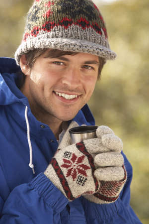 Young Man Relaxing With Thermos Flask In Autumn Landscape photo