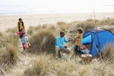 Young Family Relaxing On Beach Camping Holiday photo