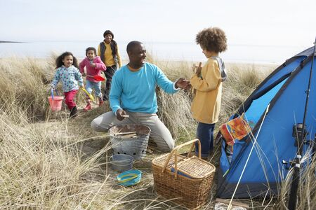 Young Family Relaxing On Beach Camping Holiday Stock Photo - 10199275
