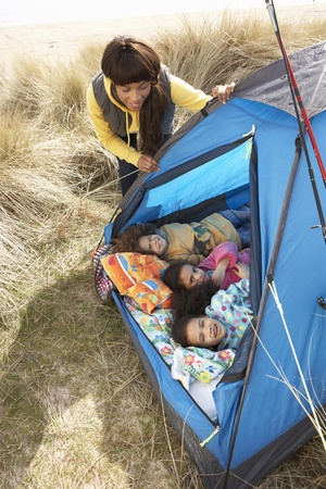 and four of the year: Young Family Relaxing Inside Tent On Camping Holiday