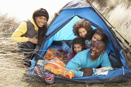Young Family Relaxing Inside Tent On Camping Holiday Stock Photo - 10199310