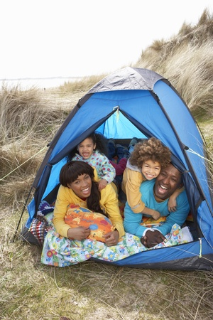 Young Family Relaxing Inside Tent On Camping Holiday photo
