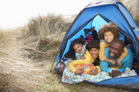 Young Family Relaxing Inside Tent On Camping Holiday Stock Photo - 10199266