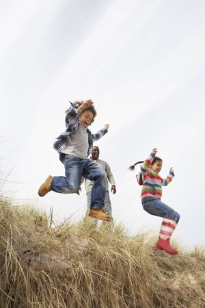 Father And Children Having Fun In Sand Dunes photo