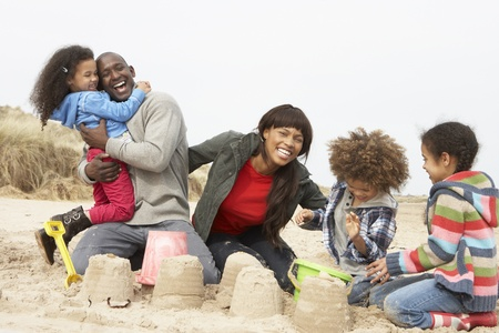 6 7 year old: Young Family Building Sandcastle On Beach Holiday Stock Photo