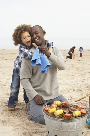 Young Family Enjoying Barbeque On Beach photo