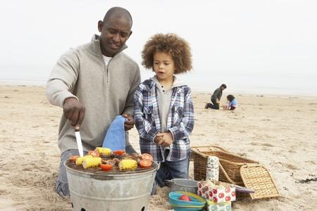 Jeune famille B�n�ficiant barbecue sur la plage Banque d'images