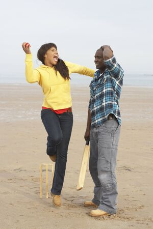 Young Couple Playing Cricket On Autumn Beach Holiday photo