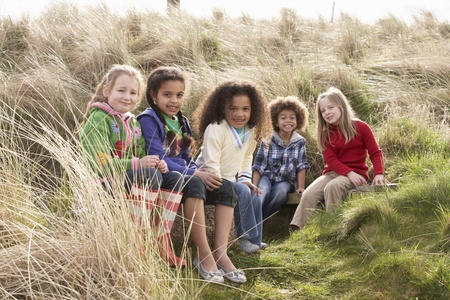 6 7 year old: Group Of Children Playing In Field Together Stock Photo
