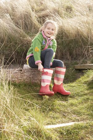 wellies: Young Girl Putting On Wellington Boots Stock Photo