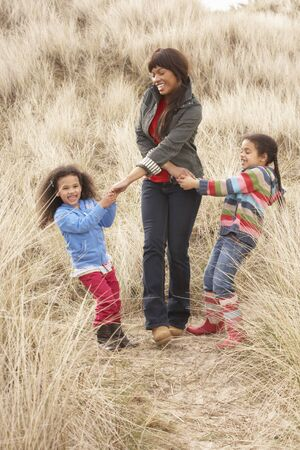 Mother And Daughters Having Fun In Sand Dunes photo