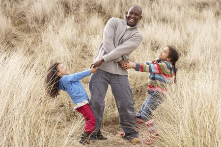 Father And Daughters Having Fun In Sand Dunes photo