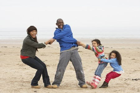 Family Having Fun On Winter Beach photo