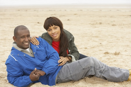 Young Couple Relaxing On Winter Beach Holiday photo