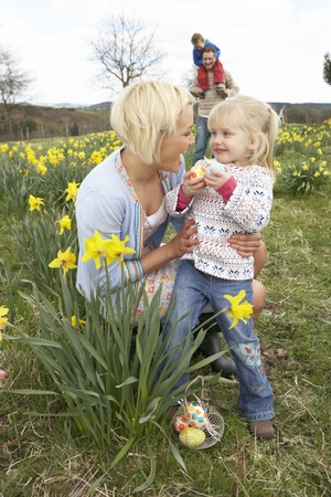and four of the year: Family On Easter Egg Hunt In Daffodil Field