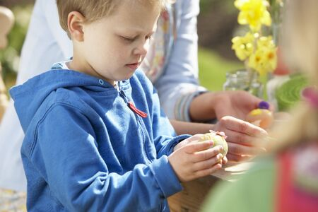 Mother And Children Decorating Easter Eggs On Table Outdoors photo
